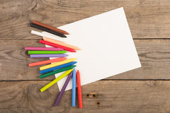 colored crayons and blank page on the wooden table Stock Photo