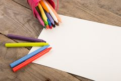 Colored crayons and blank page on the wooden table. Crayons and blank page on the wooden table royalty free stock photos