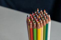 Colored crayons. Colored bunch of crayons on a white table with a blue background Stock Photos