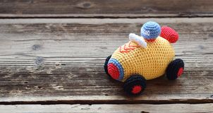 Colored crochet racing car. Toy for babies and toddlers to learn mechanical skills and colors. Handmade crafts. DIY concept. Baby toys child leisure background royalty free stock photo