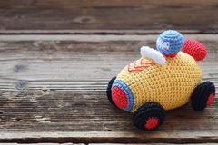 Colored crochet racing car. Toy for babies and toddlers to learn mechanical skills and colors. Handmade crafts. DIY concept. Baby toys child leisure background stock images