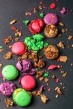 Crumbled Macaroons on black background, flat lay view. stock image