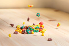 Colored crunches falling on the wooden table. Royalty Free Stock Photography