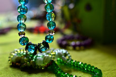 Colored crystal bracelet. Transparent bracelet and piles of bijou on a green background Royalty Free Stock Photos