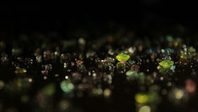 Colored crystals scattered on a table. A ray of light reveals them stock video