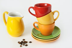 Colored cups. Three colored cups for coffee and a yellow jug of milk Royalty Free Stock Photography