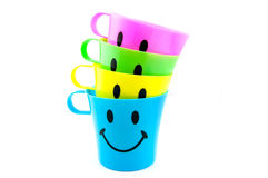 Colored cups with happy face Stock Image