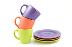 Colored cups with plates Stock Images