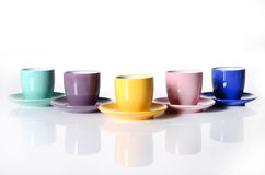 Colored cups and saucers. Five colored cups and saucers isolated on the white Stock Photography