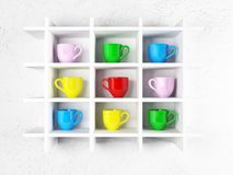 Colored cups on the shelves Royalty Free Stock Image