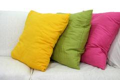 Colored Cushions. Three colored cushions on a white living room couch Royalty Free Stock Image