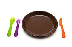 Colored cutlery and a plate Royalty Free Stock Photography