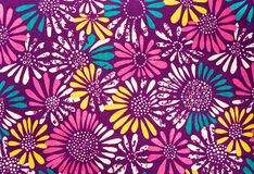 Colored daisies fabric. Colorful daisies printed on fabric on a dark background Royalty Free Stock Photo