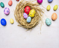 Colored decorative easter eggs with painted faces lie in a nest border ,place for text wooden rustic background top view close Stock Image