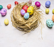 Colored decorative eggs for Easter, in the nest border place for text  wooden rustic background  close up Royalty Free Stock Photography