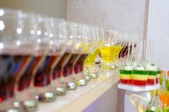 Colored desserts in glasses. Candy Bar Wedding party. Pieces of cake. Fruit on plates royalty free stock photos