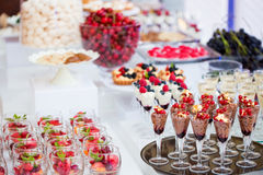 Colored desserts provided in glass jars. Multi-colored dessert decorated with fruit ready to be served in an elegant way royalty free stock image