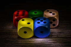 Colored dice dark background. Five multicolor dice over dark backcloth Royalty Free Stock Images