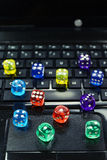 Colored  dices on keyboard - on line gambling concept Stock Images