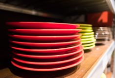 Colored dishes on a wooden bookshelf. Colored dishes red, green and white on a wooden bookshelf, on a blurred background Stock Photography