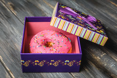 Colored donut in a beautiful purple gift box. On wooden background Stock Image