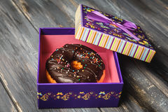 Colored donut in a beautiful purple gift box. On wooden background Royalty Free Stock Photos