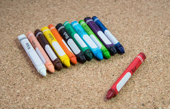 Colored drawing crayons on a cork board Royalty Free Stock Image
