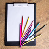 Colored drawing pencils and clipboard with blank paper on wooden Royalty Free Stock Image
