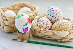 Colored drawings on eggs. Easter eggs in a wicker basket on a wooden table Colored drawings royalty free stock images