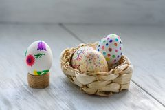 Colored drawings on eggs. Easter eggs in a wicker basket on a wooden table Colored drawings stock photo