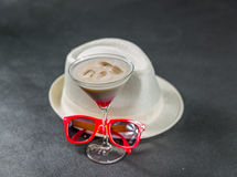 Colored drink, a combination of red, beige and violet, martini g. Lass, black sunglasses, white stylish hat, party set Royalty Free Stock Image