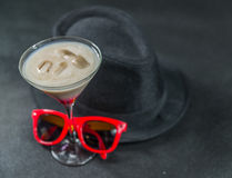Colored drink, a combination of red, beige and violet, martini g. Lass, red sunglasses, black stylish hat, party set Stock Image