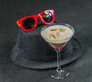 Colored drink, a combination of red, beige and violet, martini g. Lass, red sunglasses, black stylish hat, party set Stock Photography