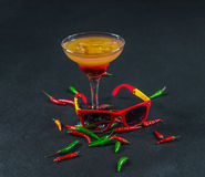 Colored drink, a combination of red orange, lemon, martini glass. Brown sunglasses, red and green peppers, party set Stock Photography