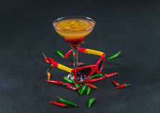 Colored drink, a combination of red orange, lemon, martini glass. Brown sunglasses, red and green peppers, party set Stock Photo