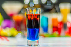 Colored drink in glass for shots, a combination of blue with red Royalty Free Stock Photography