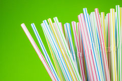Colored drinking straws on green background Stock Photo
