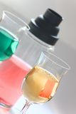 Colored drinks - cocktail set. A shaker with red drink and two glasses with yellow and green drinks Stock Photos