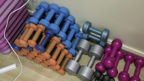 Colored dumbbells in the gym. Colorful dumbbells are in the gym stock video