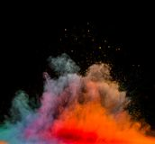 Colored dust explosion on black background Stock Photos