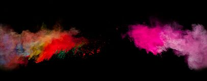 Colored dust. Freeze motion of colored dust explosion isolated on black background Stock Image