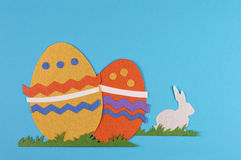 Colored easter egg and rabbit. Colorful eggs with grass and rabbits drawn and cut on paper, easter egg on a blue background stock photography