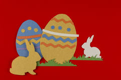 Colored easter egg and rabbit. Colorful eggs with grass and rabbits drawn and cut on paper, easter egg on a red background stock photos