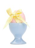 Colored easter egg with yellow ribbon in egg cup Royalty Free Stock Photo