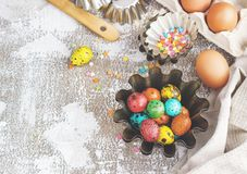 Colored easter eggs and baking molds on a light canvas background,place for text Stock Images