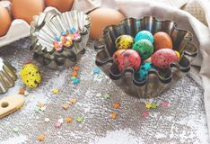 Colored easter eggs and baking molds on a light canvas background,place for text Stock Photo