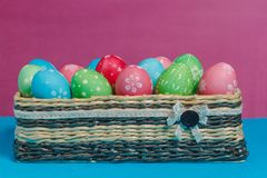 Colored Easter eggs in a basket on a blue-pink background. Royalty Free Stock Photo