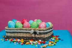 Colored Easter eggs in a basket on a blue-pink background. Stock Photos
