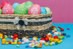 Colored Easter eggs in a basket on a blue-pink background. Royalty Free Stock Photography