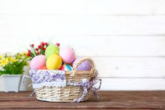 Colored easter eggs in the basket and spring flowers on wooden background. Greeting card Royalty Free Stock Image
